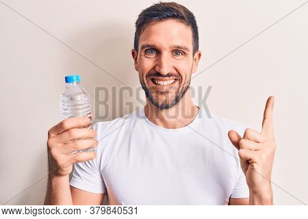 Young handsome man drinking bottle of water to refreshment over isolated white background smiling happy pointing with hand and finger to the side