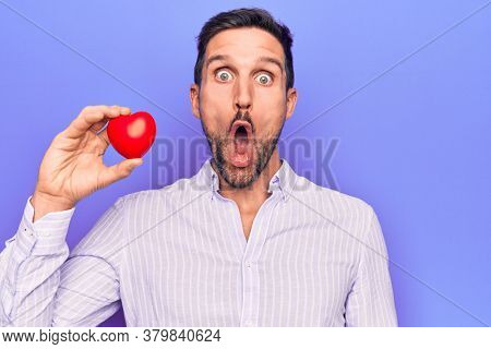 Young handsome man asking for health care holding red heart over isolated purple background scared and amazed with open mouth for surprise, disbelief face