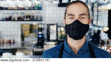Portrait Of Caucasian Young Handsome Man Barman In Mask And Apron Standing In Cafe, Looking At Camer