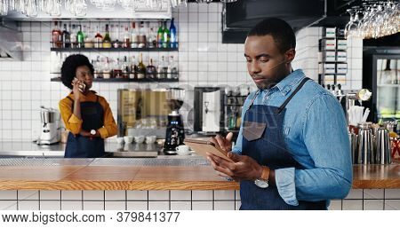 Male African American Barmen Using Tablet Device In Cafe. Handsome Man Waiter Tapping And Scrolling