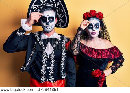 Young couple wearing mexican day of the dead costume over yellow worried and stressed about a problem with hand on forehead, nervous and anxious for crisis