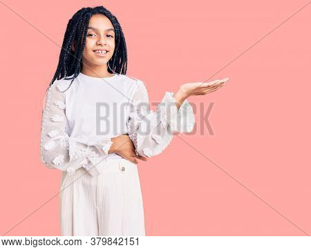 Cute african american girl wearing casual white tshirt smiling cheerful presenting and pointing with palm of hand looking at the camera.
