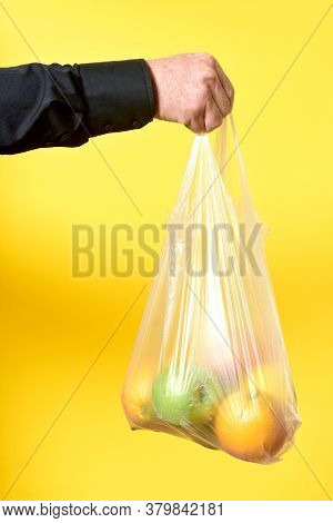 Bag Of Platic With Fruits On Yellow Background