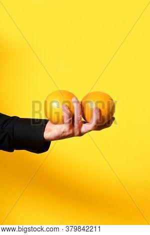 Hand Holding A Orange Frut On Yellow Background
