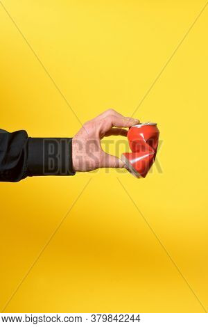 A Hand Crushing A Can Of Drink