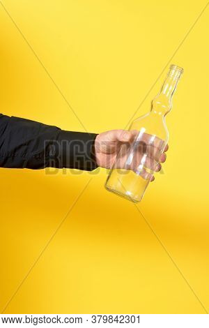 Man Holding A Transparent Bottle On Yellow Background