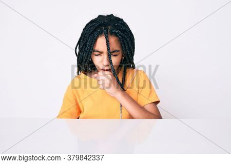 Young african american girl child with braids wearing casual yellow tshirt feeling unwell and coughing as symptom for cold or bronchitis. health care concept.