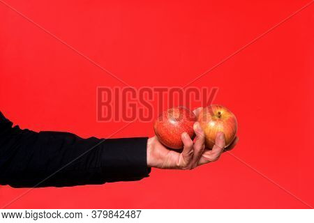 Hand Holding A Two Apple On Red Background