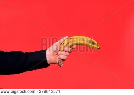 Hand Holding A Banana On Red Background