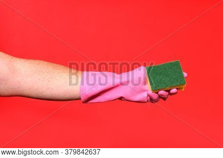 Hand With Glove Hoding Scourer On Red Background