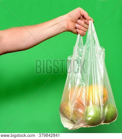A Hand Holding A Bag Of Fruits On Green