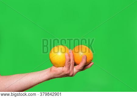 Hand Holding A Two Oranges Fruit On Green Background