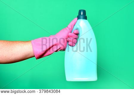 Hand With Glove And Plastic Bottle Soap On Green Background