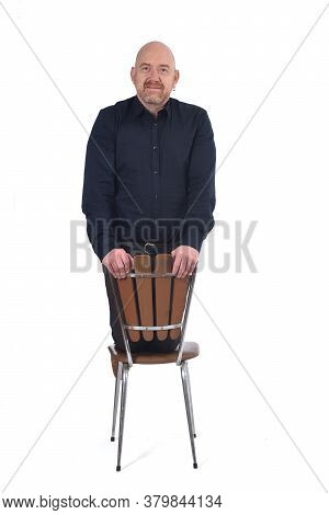 Bald Man Sitting On His Knees In A Chair