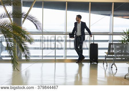 Businessman on mission waits for his connecting flight in airport waiting area