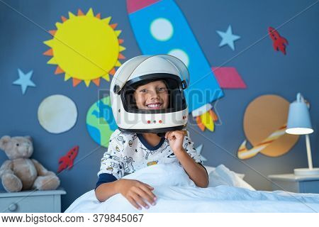 Portrait of happy child wearing astronaut helmet in outer space decorated bedroom. Smiling kid ready to sleep with planets and rocket. Excited boy pretending to be an astronaut looking at camera.