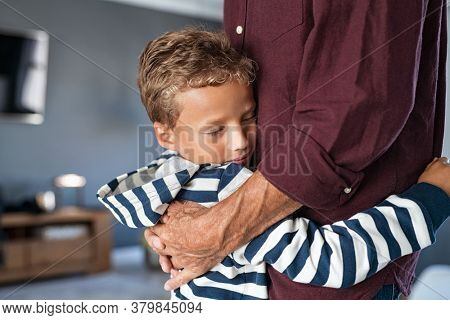 Grandchild giving a warm hug to grandfather at home. Attached cute little boy embracing senior man at home with copy space. Young grandson with closed eyes feeling relieved on hugging old granddad.