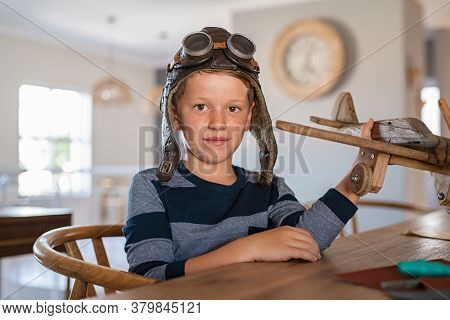 Portrait of little boy wearing pilot helmet playing with wooden airplane. School kid playing with wooden plane while looking at camera. Cute child holding handmade airplane model with aviator helmet.