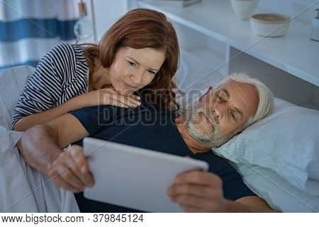 Senior couple watching video with digital tablet in the dark before sleeping. Mature man showing digital tablet to wife while lying on bed together late in night. Sleepy couple using computer.