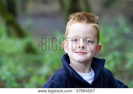 Little Boy Smiling In The Woods