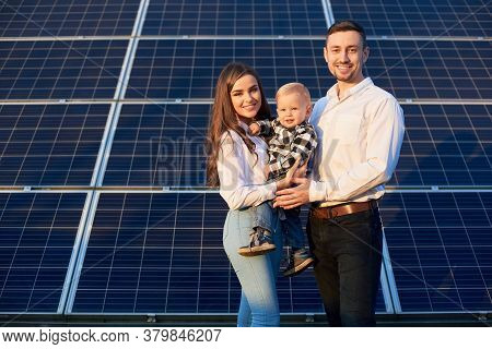 Portrait Of A Beautiful Young Family, Smiling, Standing Together Near Photovoltaic Solar Module On A