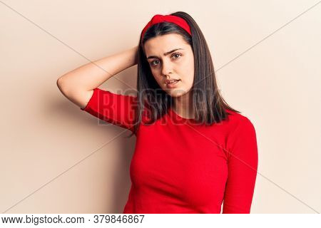 Young beautiful girl wearing casual t shirt and diadem confuse and wonder about question. uncertain with doubt, thinking with hand on head. pensive concept.
