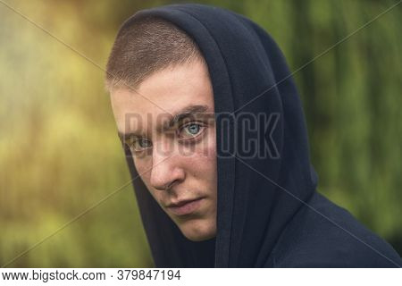 Portrait Of A Serious Young Man In A Black Hoodie