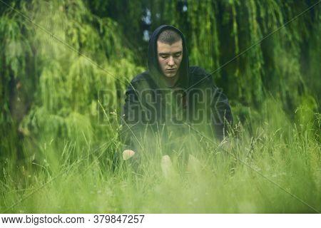Portrait Of A Sad, Crouching Man In A Black Hoodie