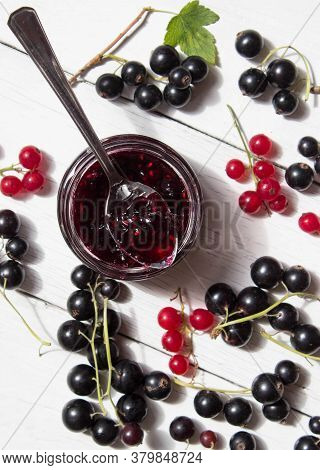Jar Of Homemade Currant Jam With Spoon. Fresh Berries Black And Red Currant On White Wooden Backgrou