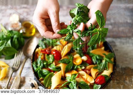 Hands Of A Chef With Basil For Cooking Italian Pasta. Cooking One Pan Pasta.