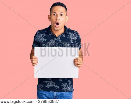 Young handsome latin man holding cardboard banner with blank space scared and amazed with open mouth for surprise, disbelief face