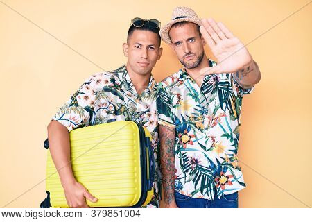 Young gay couple of two men holding suitcase going on summer vacation with open hand doing stop sign with serious and confident expression, defense gesture