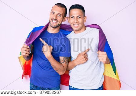 Young gay couple of two men holding rainbow lgbtq flag together smiling happy pointing with hand and finger