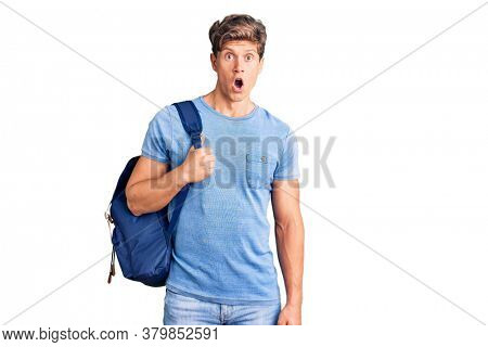 Young handsome man holding student backpack scared and amazed with open mouth for surprise, disbelief face