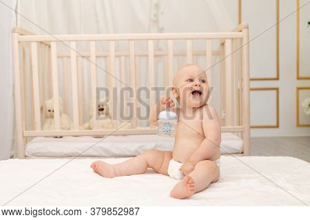 Baby Boy 8 Months Old Sitting In Diapers On A White Bed With A Bottle Of Milk At Home, Baby Food Con