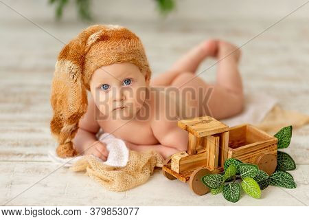 A Small Child A Boy Lies On His Stomach Naked And Looks At The Camera