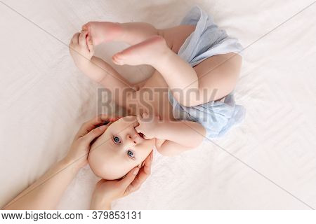 A Mother Gently Holds Her Baby Boy, The Child Is Lying On His Back On A White Bed And Holds His Hand