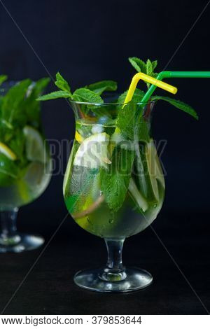 Summer Mint Lime Refreshing Cocktail Mojito With Rum And Ice In Glass On Black Background. Mojito Co
