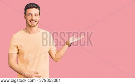 Handsome young man with bear wearing casual yellow tshirt smiling cheerful presenting and pointing with palm of hand looking at the camera.