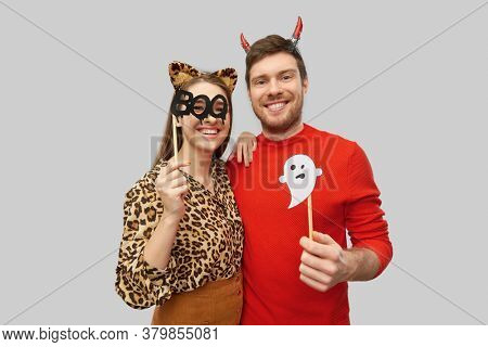 holiday, photo booth and people concept - happy smiling couple in halloween costumes of devil and leopard with party accessories over grey background