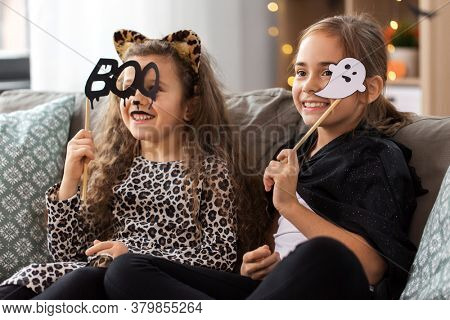 halloween, holiday and childhood concept - smiling little girls in costumes with party props at home