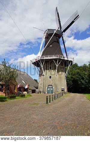 Eenrum, The Netherland - July 15, 2020: Historical Dutch Flour Mill 'de Lelie' Against A Clouded Sky