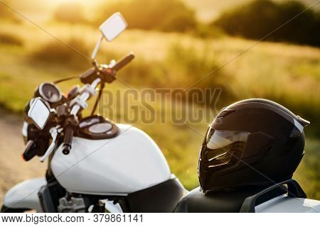 A Motorcycle Helmet Lies On A Motorcycle Seat In The Rays Of The Setting Sun With Selective Focus.
