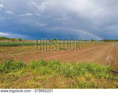 A Beautiful Picturesque Scenic Landscape Of Arable Agricultural Land After The Rain And A Colorful R