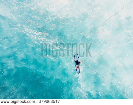 Aerial View Of Surfer On Surfboard Rowing In Blue Ocean. Top View