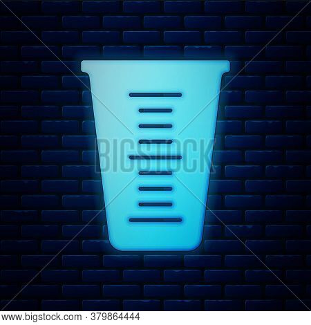 Glowing Neon Measuring Cup To Measure Dry And Liquid Food Icon Isolated On Brick Wall Background. Pl