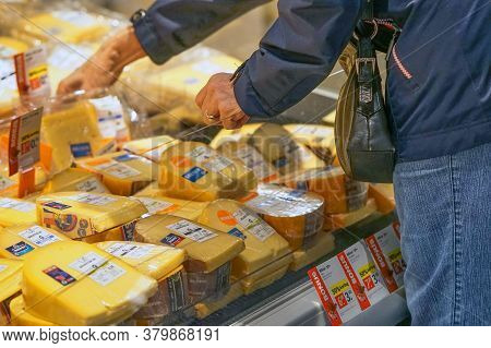 Closeup Elderly Womans Hands Picking Cheese Inside Superstore. Old Woman Choose Cheese In Supermarke