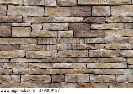 Natural Tan And Brown Thin Cut Stacked Stone Block Wall With Shadows And Straight Lines Suitable For