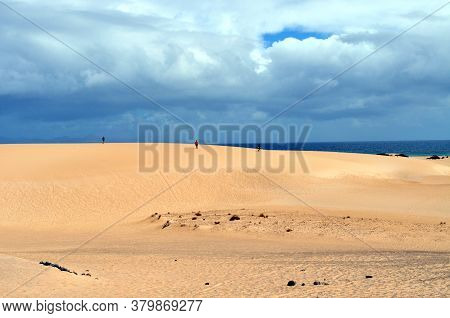 People Walks On Huge Sand Dunes With Clouds Hanging Over Them And The Blue Ocean On The Horizon. Cor