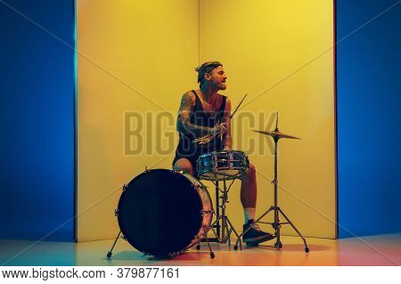 Rockstar. Young Musician With Drums Performing On Yellow Background In Neon Light. Concept Of Music,